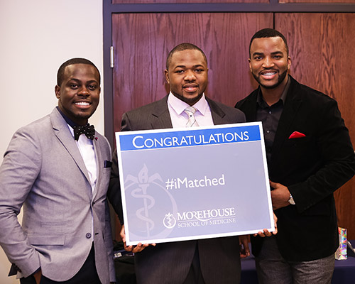A group of men holding a sign that says 'I matched'