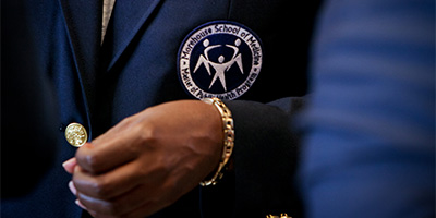 a closeup of an MPH program badge on a suit jacket