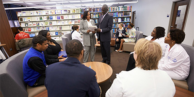 Members gathered in a library talking about a report