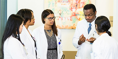 a group of physician assistants listening to a doctor