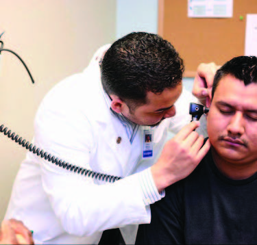 a doctor looks into a man's ear using an instrument
