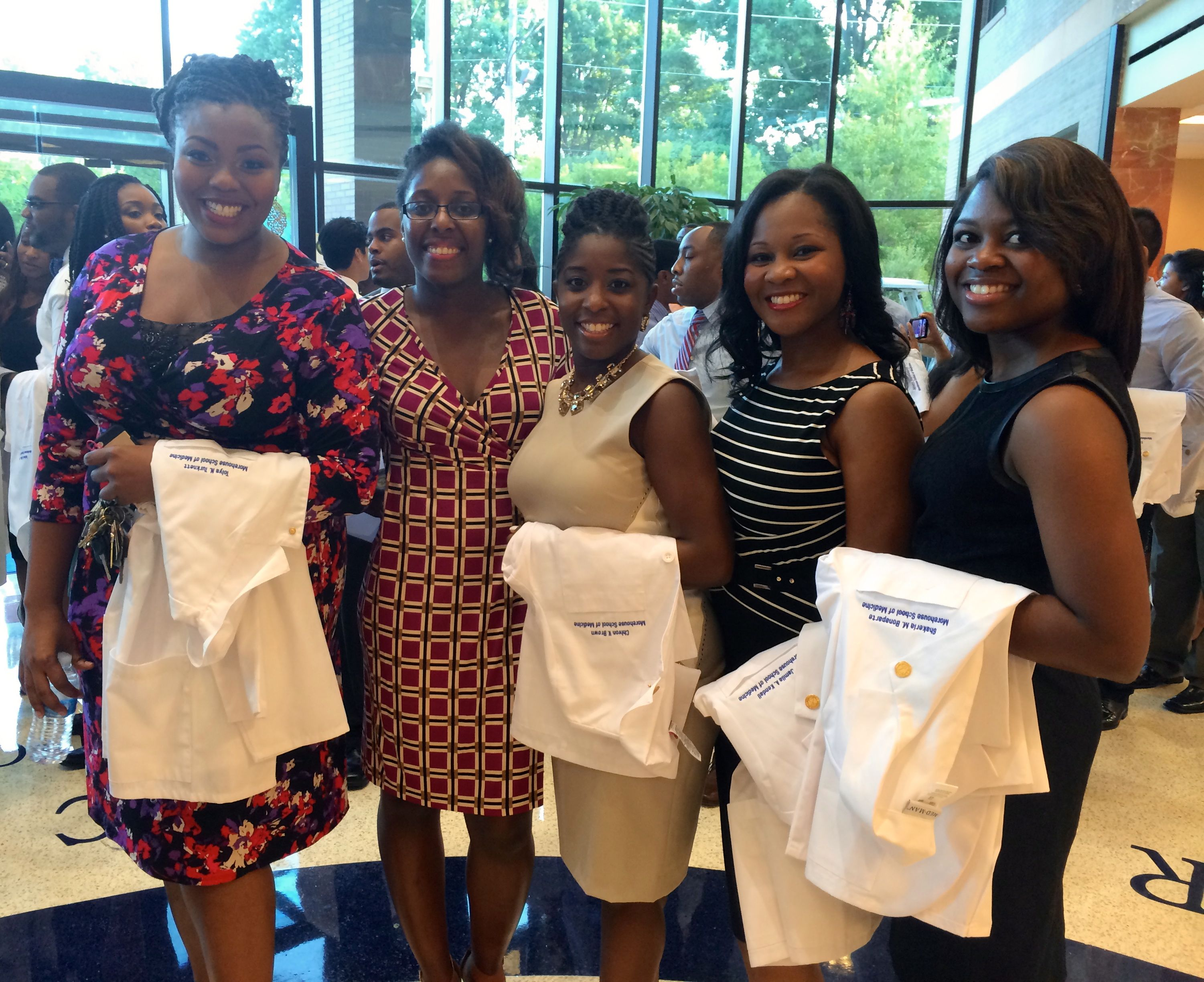 a group of APEX members holding their whitecoats