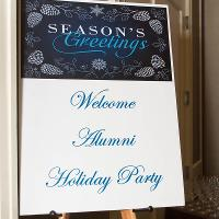 """A sign reading""""Welcome Alumni Holiday Party"""""""