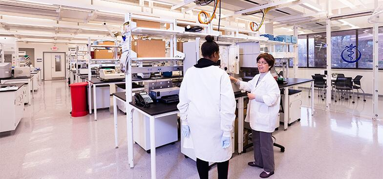 two women standing inside a lab room