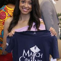 a woman holds a shirt that says March is Coming