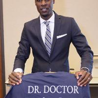 a man holds a shirt reading Dr. Doctor 19