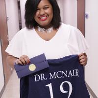 a woman holds a shirt reading Dr. McNair 19