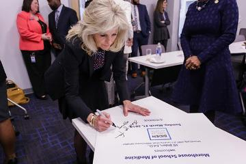 Dr. Jill Biden autographs one of the welcome signs.