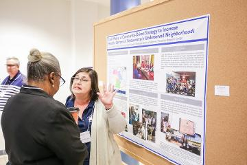 a woman gives a poster presentation