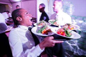 a server holds hot plates of food