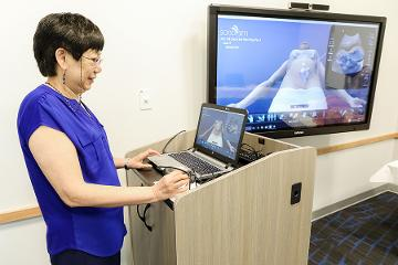 a woman gives a presentation on a screen