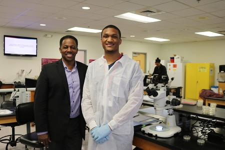 two men stand in a lab