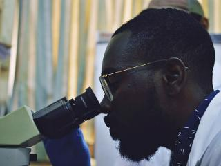 a man looks into a microscope