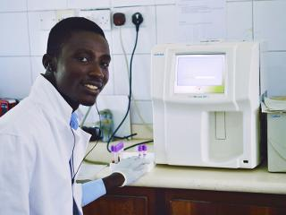 a man smiles while using lab testing equipment