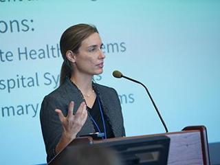 Speaker at podium with slideshow